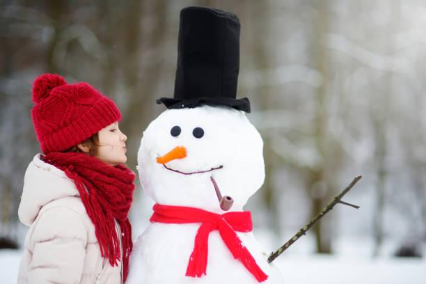 Adorable little girl building a snowman in beautiful winter park cute picture id1059569992?b=1&k=6&m=1059569992&s=612x612&w=0&h=psunolk9nu3ztzbphwts9o mzlwjiie8xawuwzwq bw=