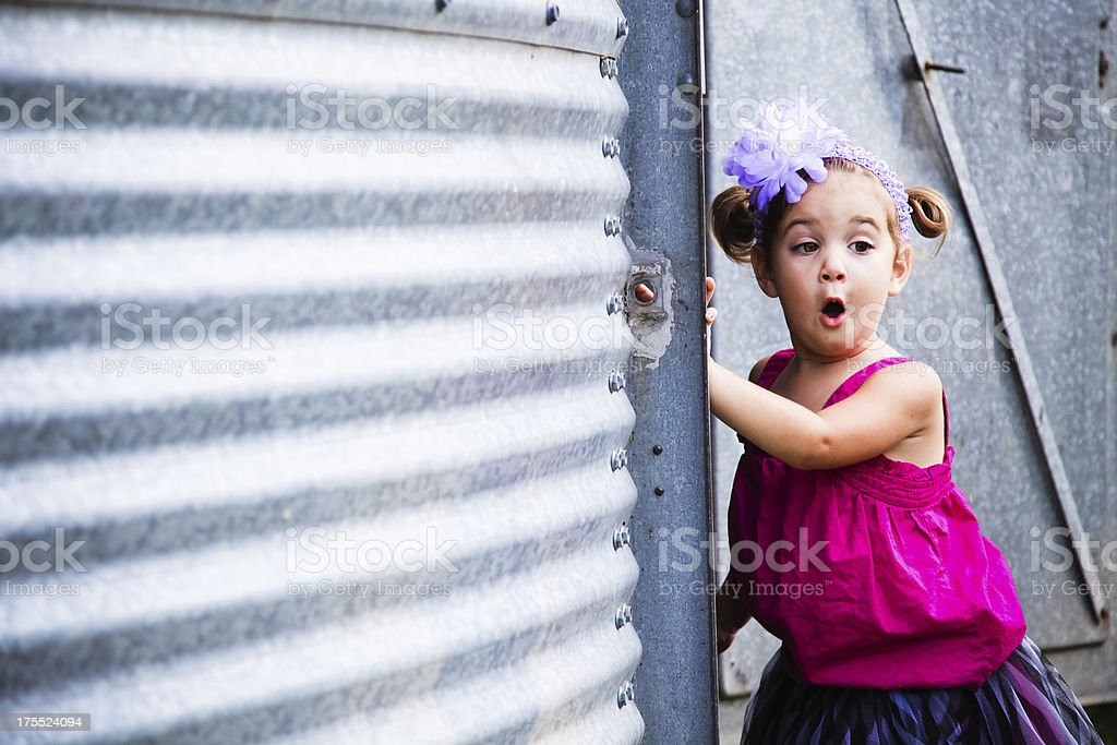 Adorable Little Girl by Metal Building Making a Face royalty-free stock photo