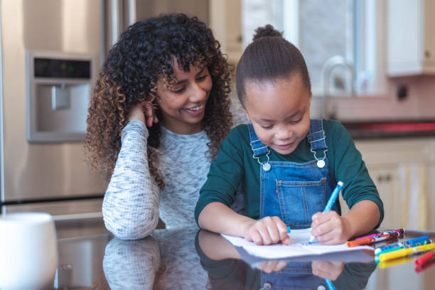 Adorable little girl colouring with her mother stock photo
