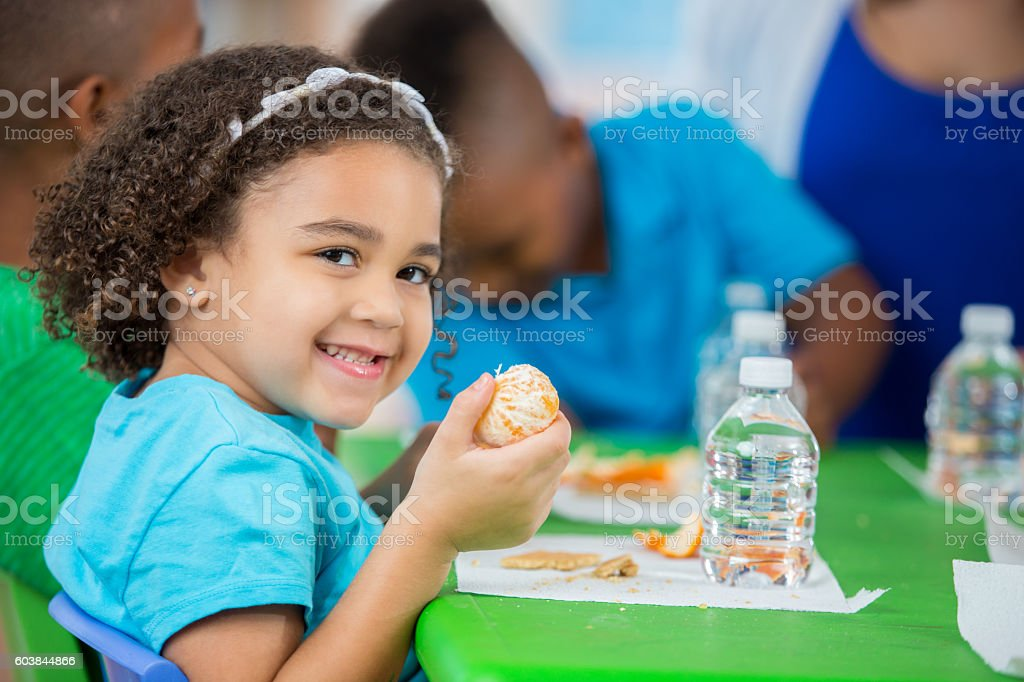 Adorable little girl eating an orange during daycare snack time stock photo