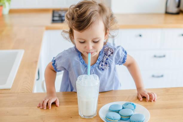 Entzückende kleine Mädchen essen blaue Makronen auf die weiße moderne Küche zu Hause – Foto