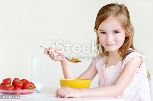istock Adorable little girl eating cereal in a kitchen 506442244