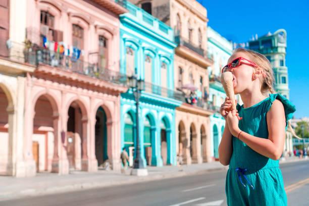 entzückende kleine mädchen essen eis in beliebten gegend in alt-havanna, kuba. porträt von cutiest kind im freien auf einer straße in havanna - urlaub in kuba stock-fotos und bilder
