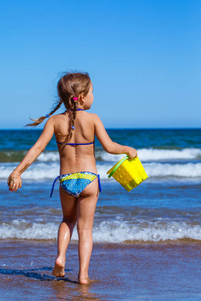 adorable petite fille profiter de la plage de valence de sandy - fille dos photos et images de collection