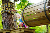Adorable little girl enjoying her time in climbing adventure park on warm and sunny summer day. Summer activities for young kids. Child having fun on school vacations.