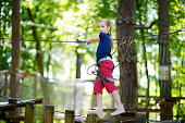 Adorable little girl enjoying her time in climbing adventure park on warm and sunny summer day