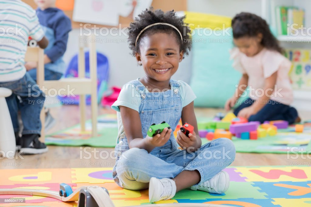 Adorable little girl enjoys time at day care stock photo