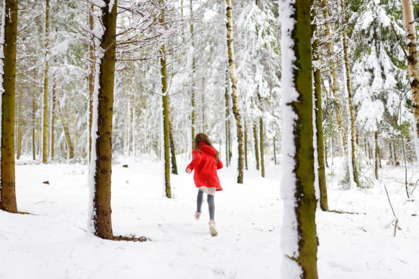 Adorable little girl having fun in beautiful winter park. Cute child playing in a snow. stock photo