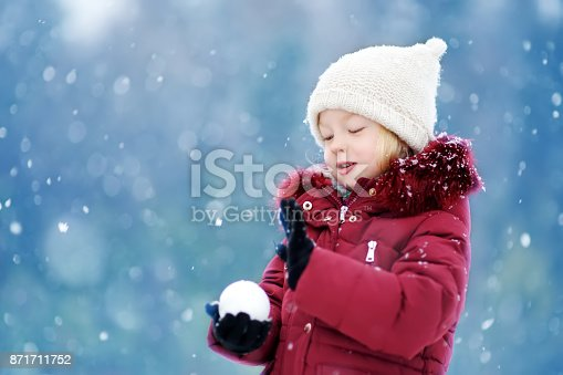 istock Adorable little girl having fun in beautiful winter park. Cute child playing in a snow. 871711752