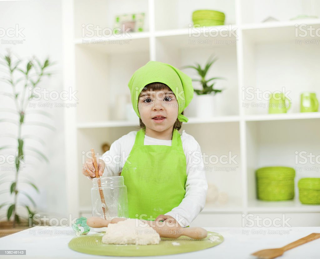 Adorable little girl having fun in the kitchen stock photo