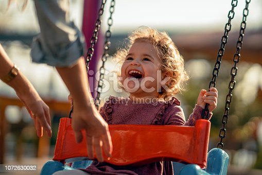 Adorable little girl having fun on a swing.