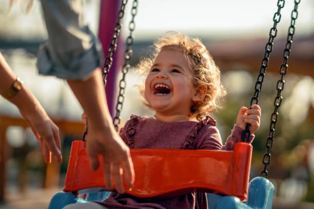 adorable little girl having fun on a swing - balouço imagens e fotografias de stock