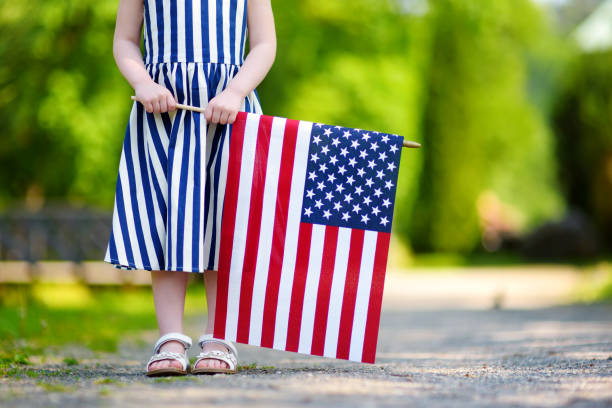 Adorable little girl holding american flag outdoors on beautiful summer day stock photo