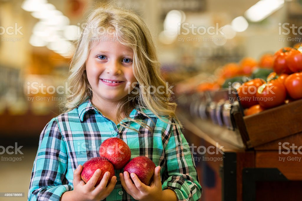 Adorable little girl holding apples in grocery store produce section stock photo