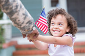 Beautiful little girl smiles up at her military dad while holding his hand. She is also holding a small US flag.