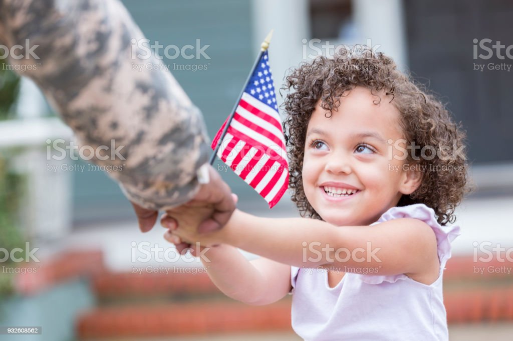 Adorable little girl holds her military dad's hand stock photo