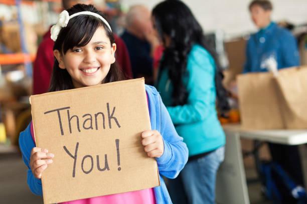 adorable little girl holds thank you sign during food drive - fondazione di beneficienza foto e immagini stock