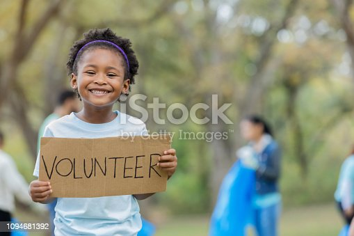 An adorable preschool age little girl stands outdoors in a public park.  There are adults picking up litter in the background as she holds up a sign that says,