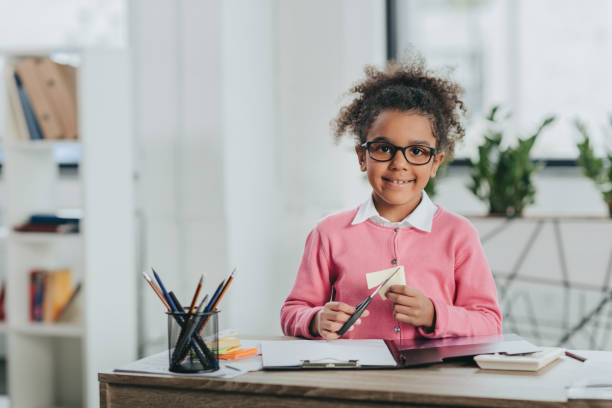 Adorable little girl in eyeglasses holding scissors and smiling at camera stock photo