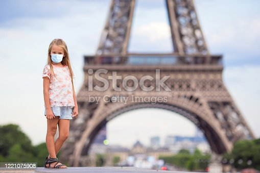 Adorable little girl wearing a mask for prevent virus in Paris background the Eiffel tower in France