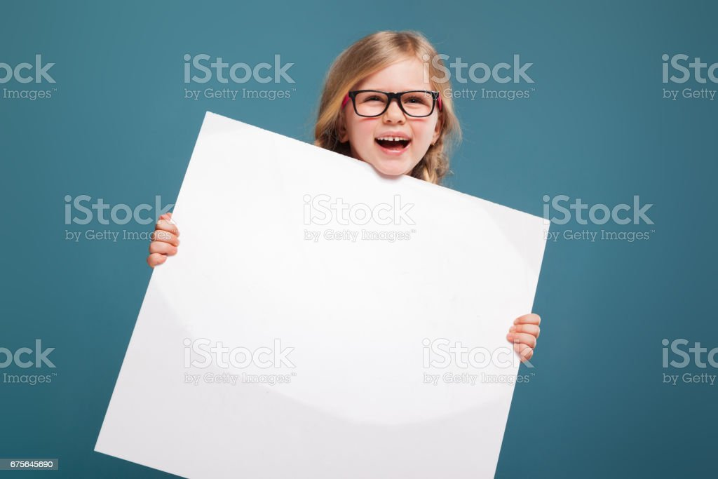 Adorable little girl in pink shirt, black trousers and glasses holds empty poster royalty-free stock photo