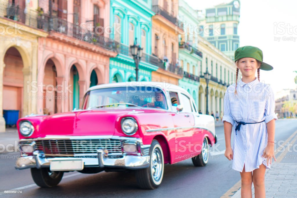 Adorable little girl in popular area in Old Havana, Cuba. Portrait of kid background vintage classic american car royalty-free 스톡 사진