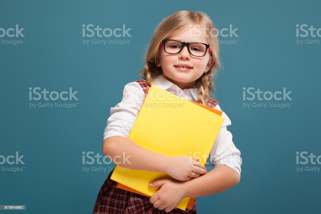 Adorable little girl in red dress, white shirt and glasses holds paper folder royalty-free stock photo