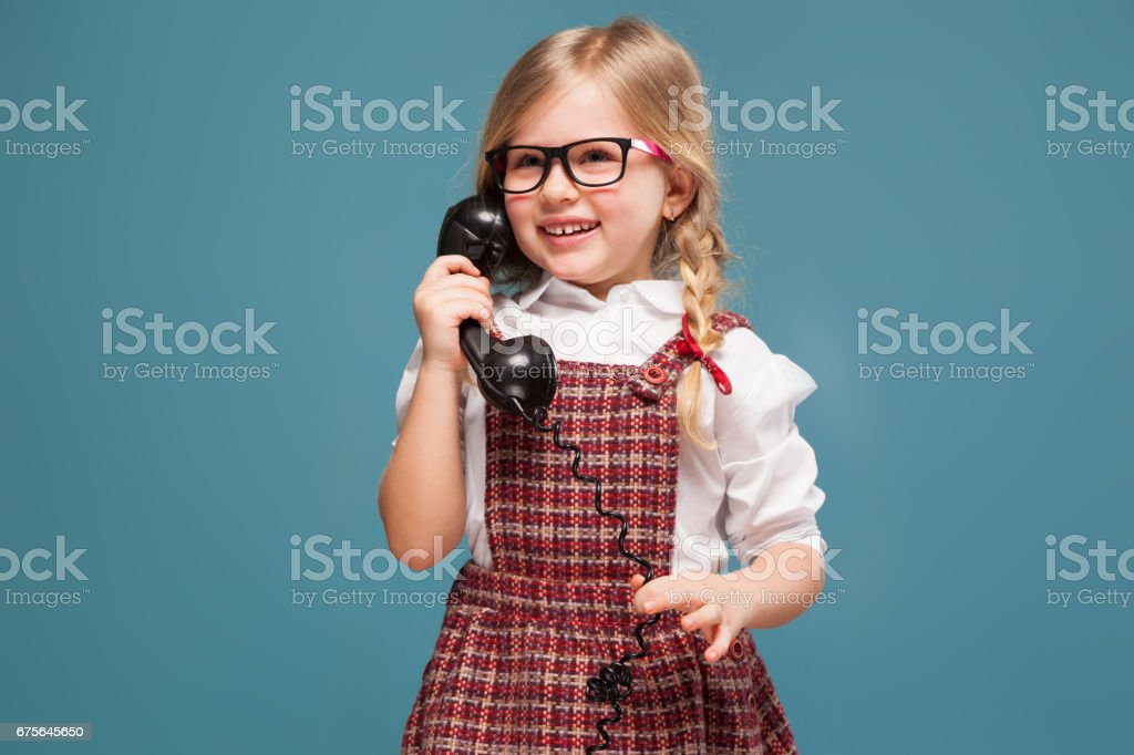 Adorable little girl in red dress, white shirt and glasses holds phone handset royalty-free stock photo