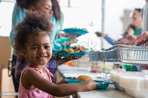 istock Adorable little girl in soup kitchen 626891350