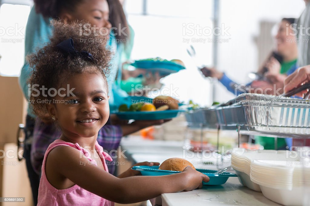 Adorable little girl in soup kitchen - foto de stock