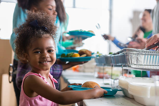 Adorable little girl in soup kitchen stock photo
