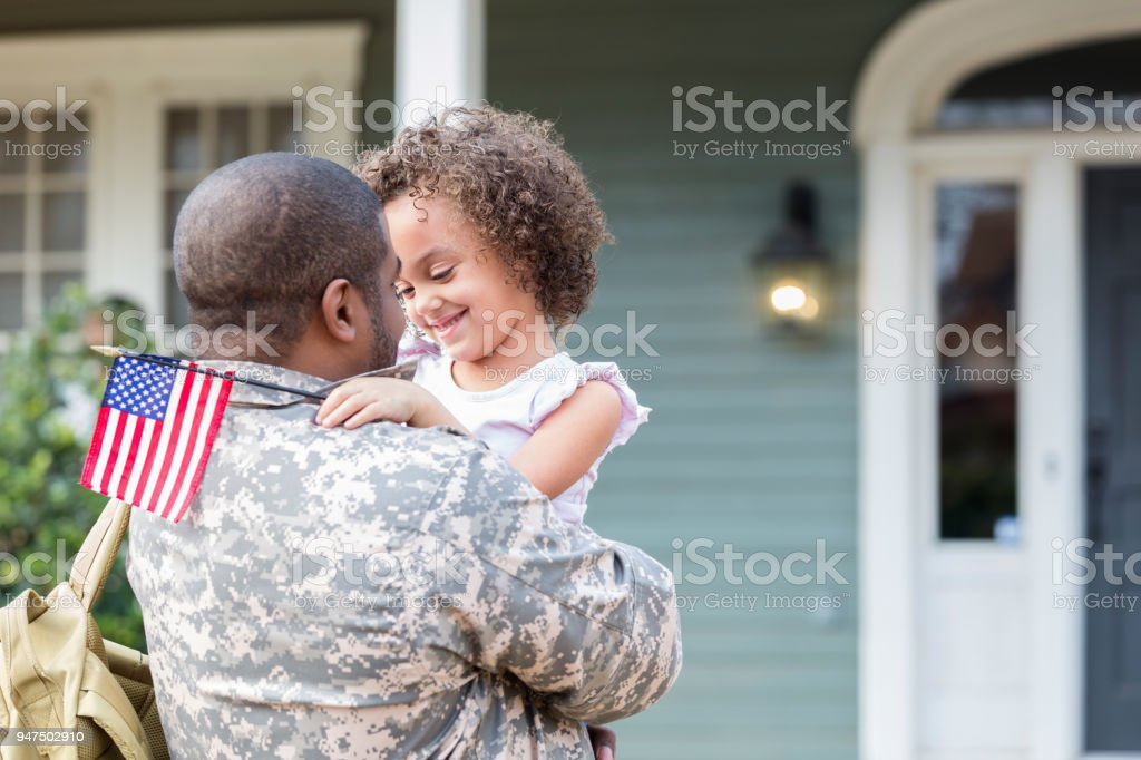 Adorable little girl is excited to see army dad stock photo