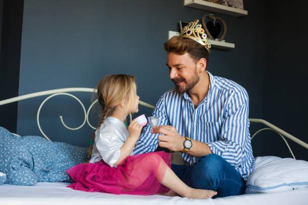 Adorable niña está teniendo té fiesta con su padre - foto de stock