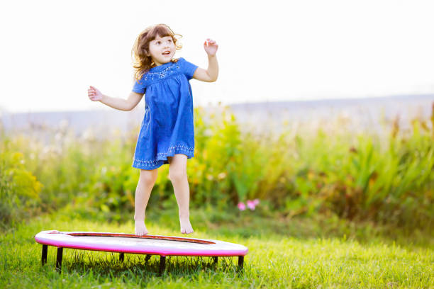 Adorable little girl jumping on a trampoline outdoors. stock photo