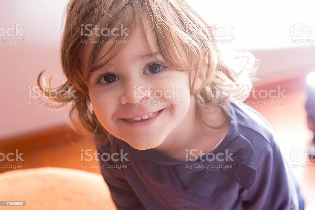 Adorable little girl looking at camera at home stock photo