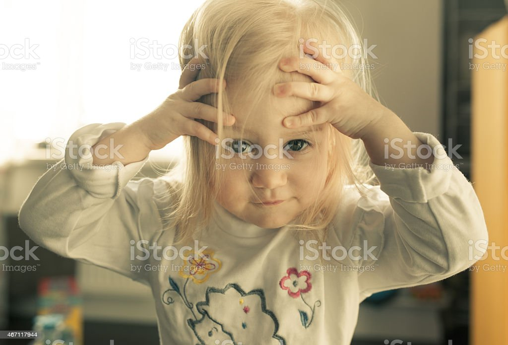 Adorable little girl looking directly at the camera. stock photo