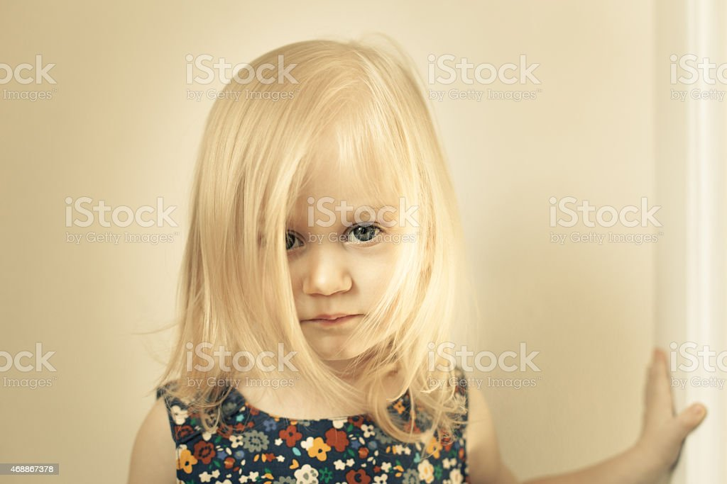 Adorable little girl looking directly at the camera stock photo