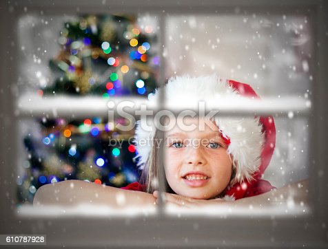 istock Adorable little girl looking through window, waiting for Santa 610787928