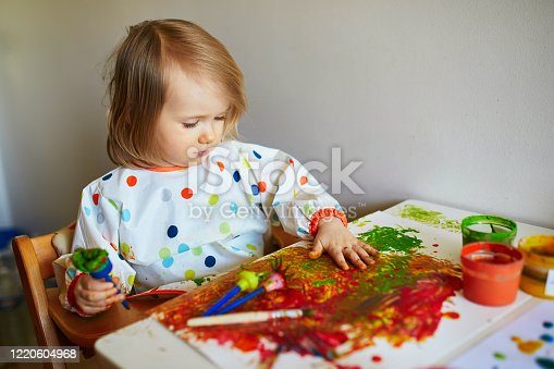 678159134 istock photo Adorable little girl painting with brushes and fingers 1220604968