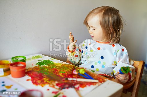 678159134 istock photo Adorable little girl painting with brushes and fingers 1220605007