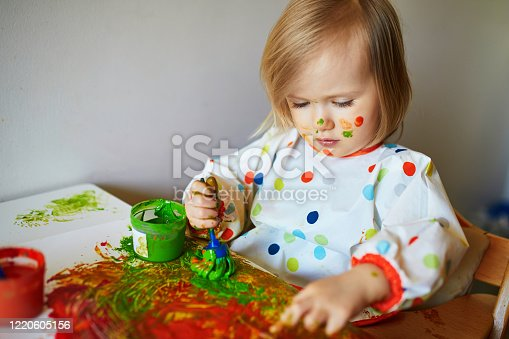 678159134 istock photo Adorable little girl painting with brushes and fingers 1220605156