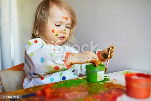 678159134 istock photo Adorable little girl painting with brushes and fingers 1220605201