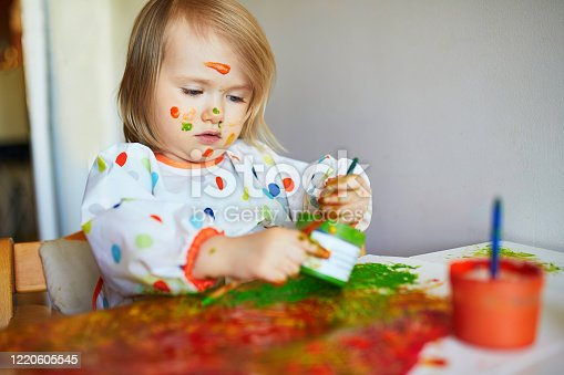 678159134 istock photo Adorable little girl painting with brushes and fingers 1220605545