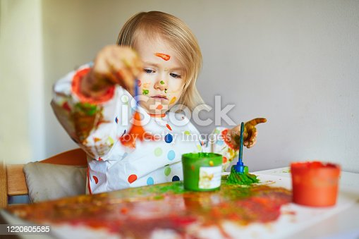 678159134 istock photo Adorable little girl painting with brushes and fingers 1220605585