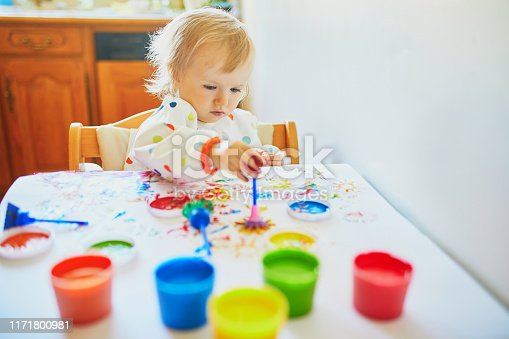 istock Adorable little girl painting with fingers 1171800981