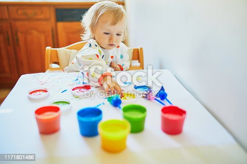 istock Adorable little girl painting with fingers 1171801486