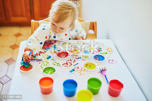 istock Adorable little girl painting with fingers 1171801489