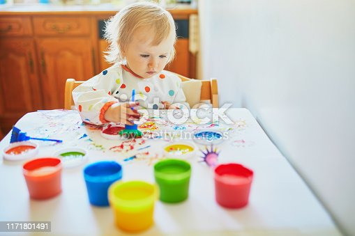 istock Adorable little girl painting with fingers 1171801491
