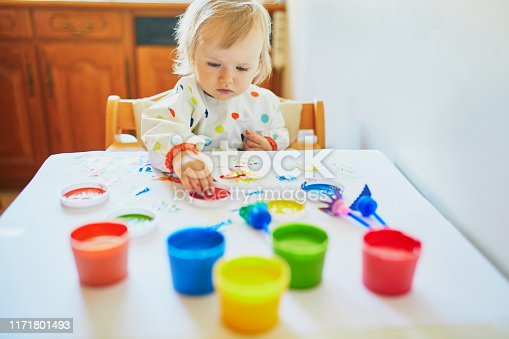 678159134 istock photo Adorable little girl painting with fingers 1171801493