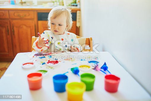 istock Adorable little girl painting with fingers 1171801495